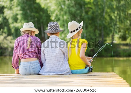 Rear view of three children sitting at bank and fishing - stock photo