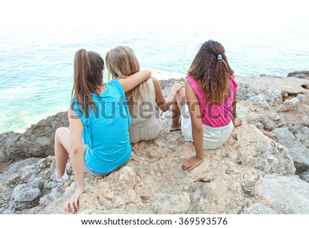 Rear view of three diverse close friends, caucasian and african american teenager girls sitting together on textured rocks, relaxing by sea, outdoors nature. Healthy holiday lifestyle, beach exterior. - stock photo