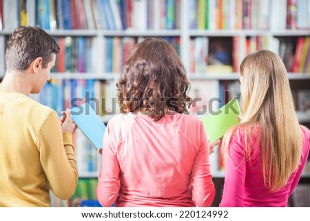 Rear view of three people choosing books from library or bookstore. - stock photo
