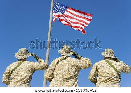 Rear view of three soldiers saluting an American flag - stock photo