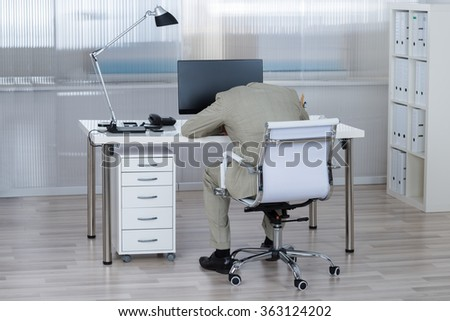 Rear view of tired businessman sleeping on desk in office - stock photo