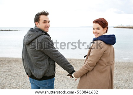 Rear view of tourist couple on a winter beach destination, holding hands by the sea on holiday destination, turning smiling looking at camera, outdoors. Recreation travel lifestyle, coastal exterior.