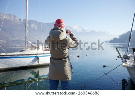 Rear view of tourist taking photo by smartphone of snowy mountain landscape and foggy lake with moored yachts near berth - stock photo