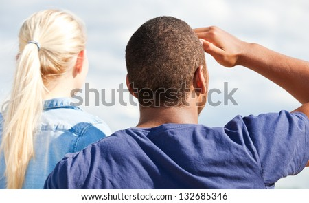 Rear view of two attractive young person staring into the distance. - stock photo