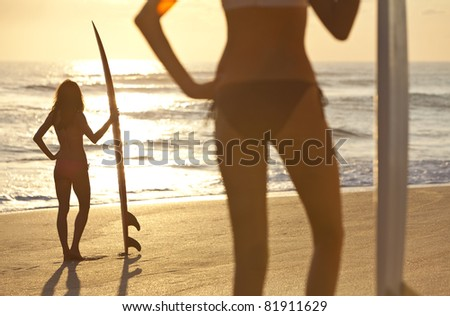Rear view of two beautiful young women surfer girls in bikinis with white surfboards on a beach at sunset