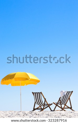 Rear view of two deck chairs and a beach umbrella with clear blue skies   - stock photo