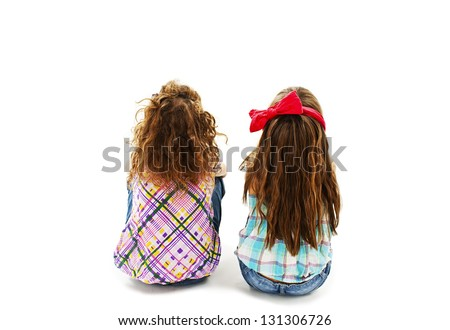 Rear view of two little girl sitting on floor and looking up. Isolated on white background - stock photo