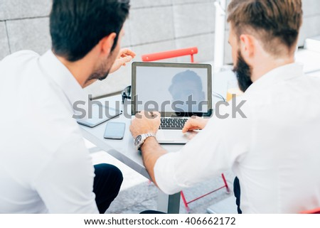 Rear view of two young bearded caucasian modern business man sitting in a bar, using smart phone and laptop, looking downward the screen, smiling - business, work, technology concept - stock photo