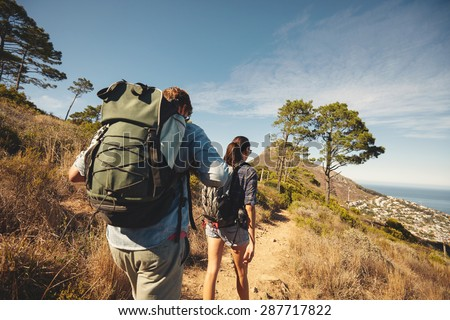 Rear view of two young people walking down the trail path on mountain. Young couple hiking with backpacks. - stock photo