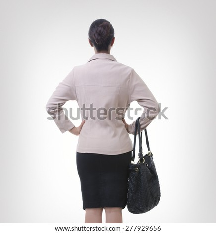 Rear view of well-dressed businesswoman over gray background