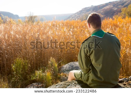 Rear View of White Boy Scout Sitting on the Huge Rock Alone Watching the Wide Brown Field on an Autumn Season. - stock photo