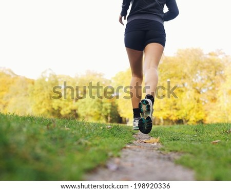 Rear view of woman athlete jogging in park. Female fitness model running outdoors - stock photo