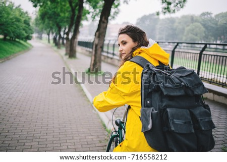 Rear view of woman cycling in the yellow raincoat