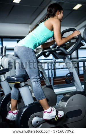 Rear view of woman doing bike exercise at gym