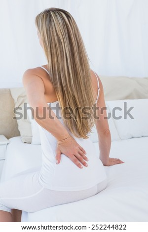 Rear view of woman getting back pain at home in the bedroom - stock photo