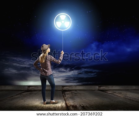 Rear view of woman holding balloon with radioactivity sign - stock photo