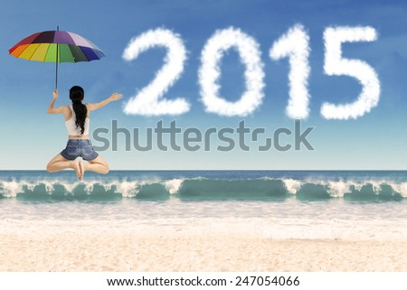 Rear view of woman holding umbrella and leaping frog style on beach celebrate new year - stock photo