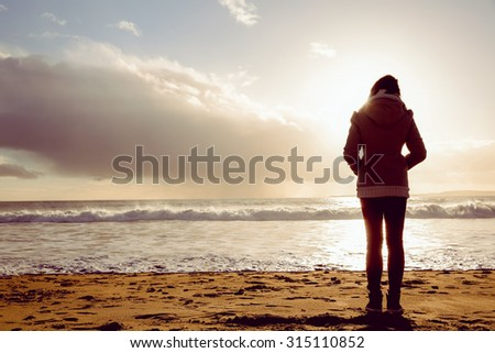 Rear view of woman looking at the sea on the beach