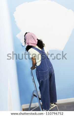 Rear view of woman on stepladder painting her new house - stock photo