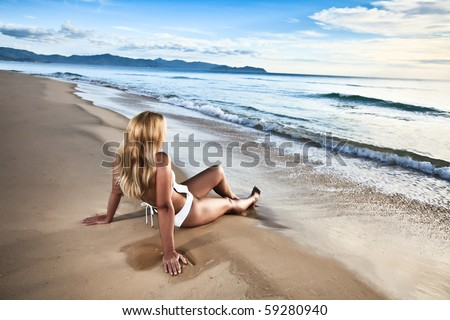 Rear view of woman on the beach at sunrise time - stock photo