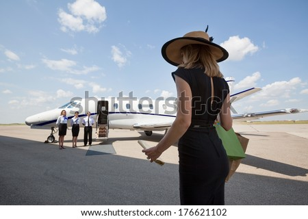 Rear view of woman walking towards pilot and stewardesses against private jet at airport terminal - stock photo
