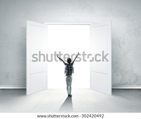 Rear view of woman with hands up entering opened door - stock photo