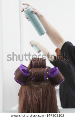 Rear view of woman with rollers getting hairsprayed by hairdresser in salon - stock photo