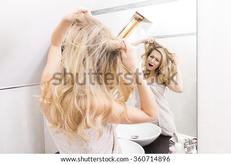 Rear View of Young Blond Woman Wrapped in Towel and Looking at Reflection of Self in Bathroom Mirror - Looking Frustrated and Upset with Hands Pulling at Hair - stock photo