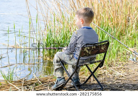 Rear View of Young Boy Sitting in Folding Chair at Edge of Pond and Fishing Patiently Amongst the Reeds