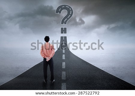 Rear view of young businessman standing on the road while looking at question sign - stock photo