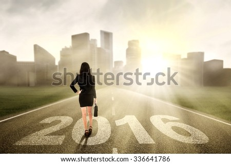 Rear view of young businesswoman carrying suitcase and walking on the road with numbers 2016 - stock photo