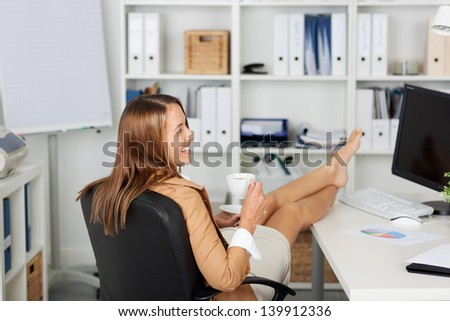 Rear view of young businesswoman having coffee at office desk - stock photo