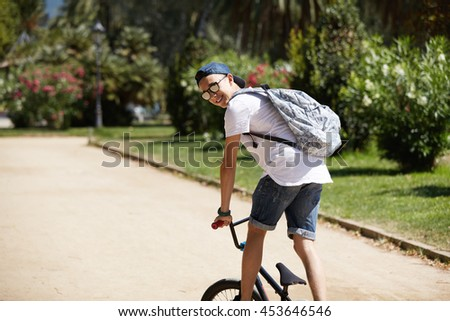 Rear view of young Caucasian BMX rider in street wear and glasses riding his bike, performing tricks, turning his head back, looking and smiling at the camera, cycling against city park background - stock photo