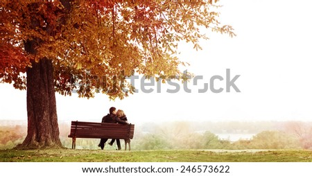 Rear View of Young Couple Sitting and Kissing on a Bench in the Beautiful Autumn Day . The man is embracing  her wife shoulder. Horizontal shot. - stock photo