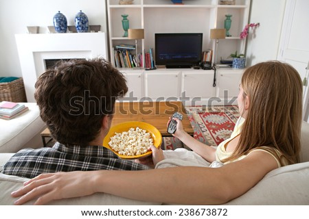 Rear view of young couple sitting together on white sofa at home using a control remote watching television, eating pop corn enjoying a night in together. Home lifestyle and entertainment technology. - stock photo