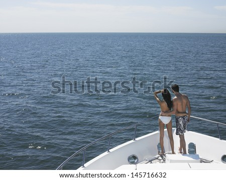 Rear view of young couple standing on bow of yacht looking at seascape - stock photo