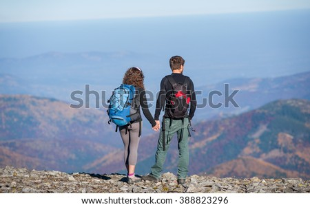 Rear view of young couple tourists with backpacks standing on the ridge of the mountain, enjoying the view of beautiful open overlook on the mountains. Couple is holding hands. Sunny autumn day.