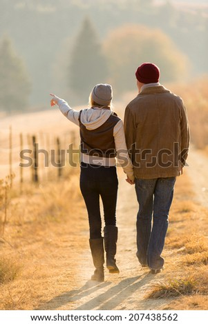 rear view of young couple walking in country road - stock photo