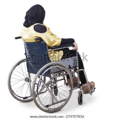 Rear view of young disabled woman sitting alone on wheelchair, isolated on white background - stock photo