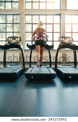 Rear view of young female running on treadmill in gym. Fitness woman jogging indoors in health club - stock photo