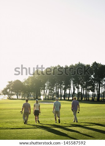 Rear view of young golfers walking on golf course - stock photo