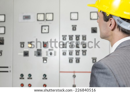 Rear view of young male supervisor examining control room in industry - stock photo