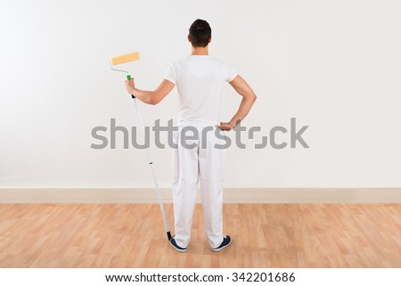 Rear view of young man holding paint roller while standing against white wall at home - stock photo