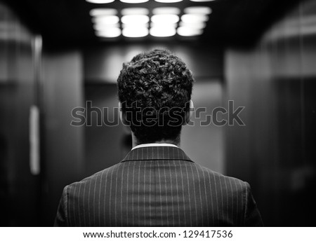 Rear view of young man in suit, black and white image - stock photo