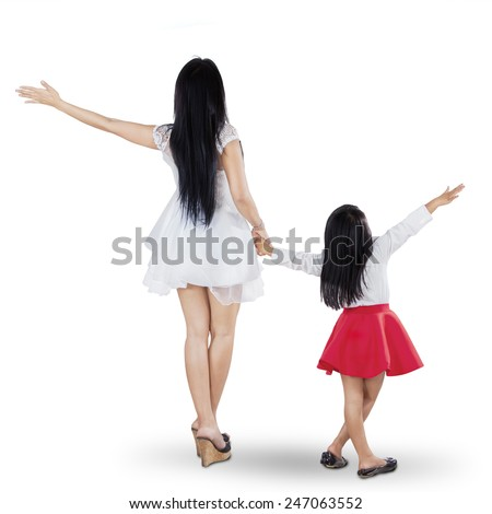 Rear view of young mother and daughter holding hands in the studio - stock photo
