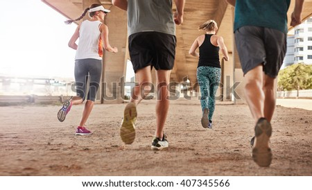 Rear view of young people running under the bridge in the city. Low angle shot of group of young men and women jogging together. - stock photo