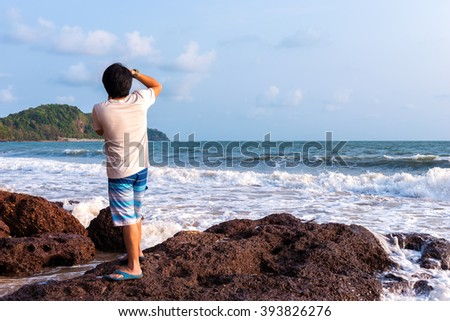 Rear view of young photographer taking view of sea