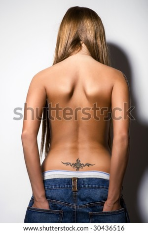 rear view of young sexy girl, nude in jeans, tattoo on back