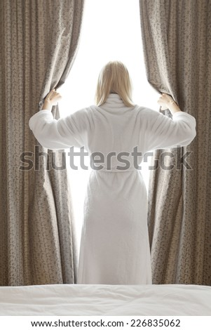 Rear view of young woman in bathrobe opening bedroom curtains at hotel room - stock photo