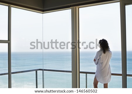 Rear view of young woman looking at ocean view from balcony at resort - stock photo